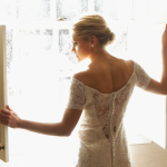 The final stage of bridal is prep is when the bride poses in her wedding dress before a window at the Woodstock Inn.